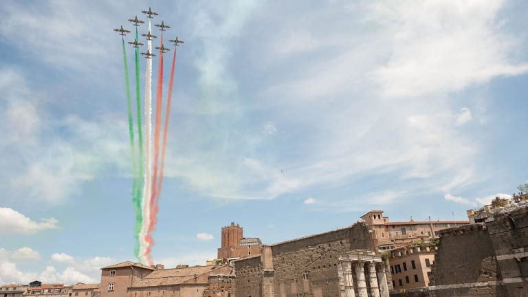 The Frecce Tricolore air squadron flies over the Via dei Fori Imperiali during the military parade to mark the founding of the Italian Republic and the 150th anniversary of Italian unification after the death of Benito Mussolini.