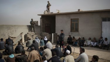 Displaced people who fled Islamic State-held territory sit outside a mosque guarded by Iraqi soldiers in Shuwayrah, south of Mosul.