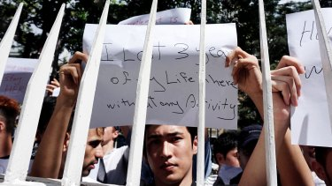 Dozens of asylum seekers hold posters during protest in front of the UNHCR office in Jakarta on Monday.
