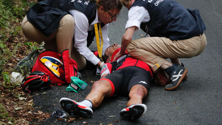 Australia's Richie Porte gets medical assistance after crashing in the descent of the Mont du Chat pass during the ninth stage of the Tour de France cycling race over 181.5 kilometers (112.8 miles) with start in Nantua and finish in Chambery, France.
