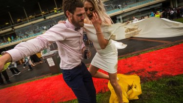 Francis Kavanagh helps his girlfriend Tiarne Coxhill across a muddy area at Cox Plate Day at Moonee Valley Racecourse.