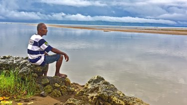 Sailosi Ramatu looks over the sea at his old village Vunidogoloa in Fiji. Each time the ocean surged through their coastal Fijian village, residents would use rafts to move from house to house.