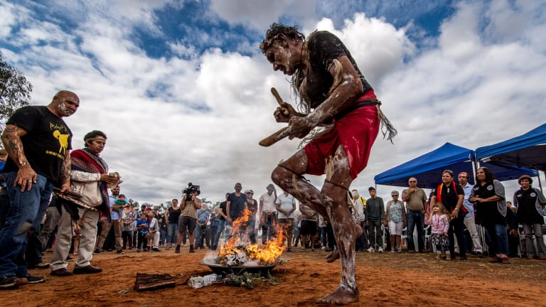 Fire and smoke are the companions of the 105 repatriated ancestors throughout their journey back to country. Mutthi Mutthi elder David Edwards performs a ceremonial dance at Balranald, NSW.