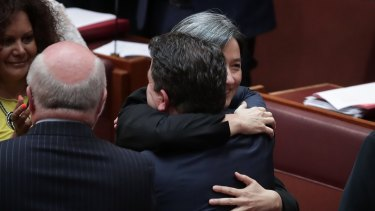 Leader of the Opposition in the Senate Penny Wong embraces Liberal senator Dean Smith after the Marriage Amendment Bill goes through the Senate on Wednesday.