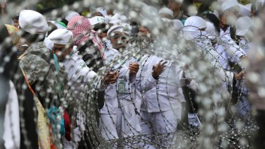 Muslim protesters are seen through razor wire barricades during a rally against the persecution of Rohingya Muslims outside the Myanmar's Embassy in Jakarta, Indonesia last week.
