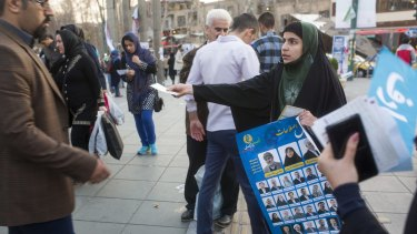 A woman distributes electoral posters in downtown Tehran earlier this year.
