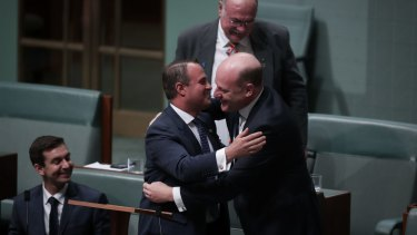 Liberal MP Tim Wilson is embraced by colleague Trent Zimmerman after his speech.
