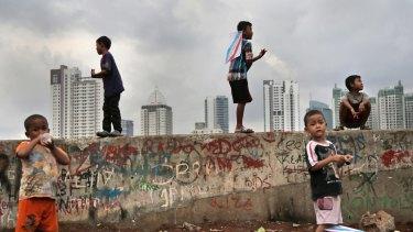 Children play against the Jakarta skyline.