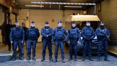 Police stand guard outside the offices of French daily newspaper Liberation as the remaining members of the Charlie Hebdo editorial staff arrive for a meeting.