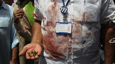 A Pakistani security official displays cartridges he collected from the scene of an attack on a bus, in Karachi, Pakistan.