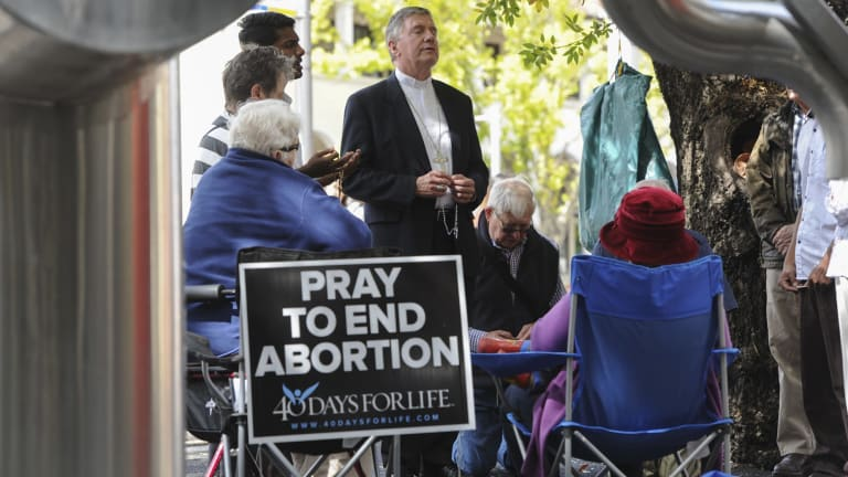 Catholic Archbishop of Canberra and Goulburn Christopher Prowse, centre, attends a prayer vigil outside the Moore Street abortion clinic in 2015.