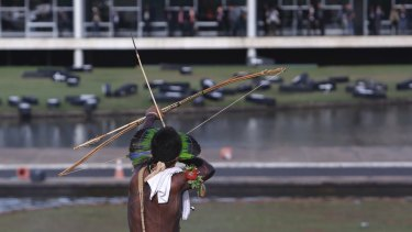 An indigenous man aims his arrow at police during a protest outside the National Congress in Brasilia, Brazil, on Tuesday.