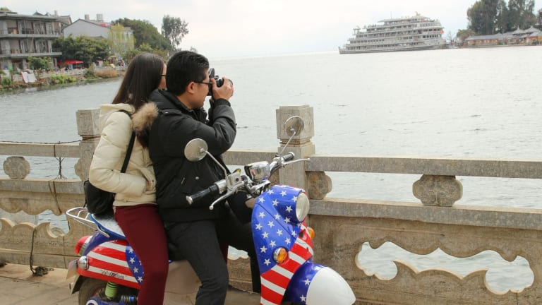A young Chinese couple take a photo in Dali, a city of 1 million that saw 24 million people visit last year.