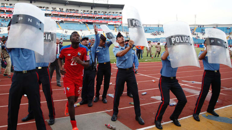 Intimidating: Police use shields to protect Panamanian Abdiel Arroyo from missiles thrown from the stands as he leaves the field at the Estadio Olimpico.