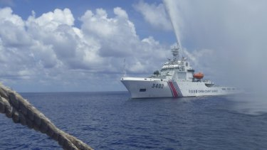 A China Coast Guard vessel approaches Filipino fishermen  off Scarborough Shoal in the South China Sea in September 2015.