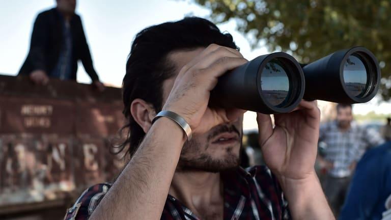 WATCHFUL: A Kurdish man monitors fighting in Kobane.