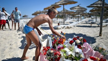 A boy leaves flowers at a memorial on the Tunisian beach where the attack took place.