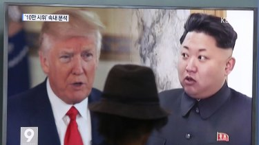 A man watches a television screen showing US President Donald Trump and North Korean leader Kim Jong-un, in South Korea.