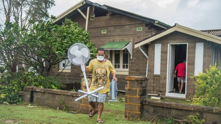 Bowen resident Joel Medil empties his cyclone-damaged home.