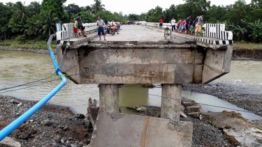 People gather on a bridge damaged by the onslaught of the flooding brought about by tropical storm Tembin.