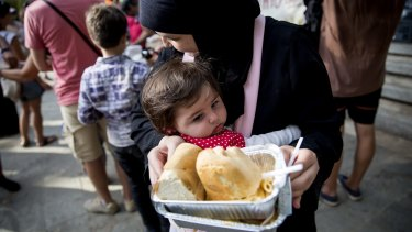 Refugees are fed in a park near the port of Mytilini in Lesbos, Greece, on Wednesday.