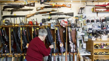 Carolyn Kellim, the owner of KC's Exchange, rearranges guns on a shelf in Roseburg, Oregon, scene of the mass shooting recently.