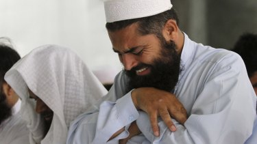 A man cries as he offers funeral prayers for the late Taliban leader Mullah Omar.