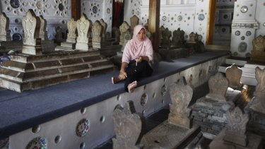 A woman sits among the tombstones at the shrine. Some conservative Muslims frown upon the burial of human beings in a house of worship and pilgrimages to such shrines.
