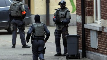 Special operations officers close down a street during a police raid in the Molenbeek neighbourhood of Brussels.