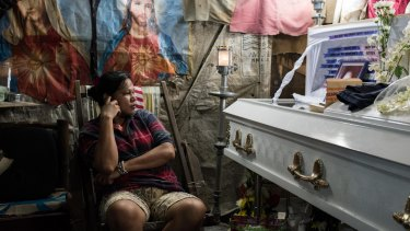 Kimberly Sailog watches over the coffin of her daughter, Christine Joy Sailog, 12, who was killed when an unidentified gunman shot at an alleged drug suspect, hitting the girl during the traditional Christmas dawn mass in a church.