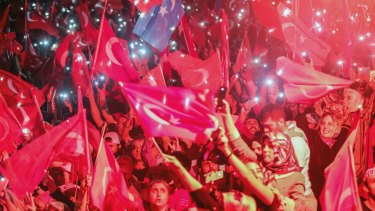 Turkish people wave flags and use their mobile phone torches during a speech by President Erdogan in August when he promised to fight those who seek to undermine the government.