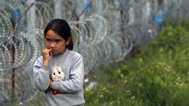 A girl walks by a border fence near Serbia's Horgos border crossing into Hungary.