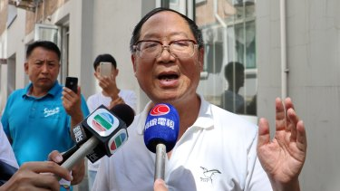 Hu Dehua, the deputy publisher of <i>Yanhuang Chunqiu</i> and the son of late liberal Chinese leader Hu Yaobang, speaks to media in front of the journal's office in Beijing, while unidentified plain-clothes men watch and film proceedings.