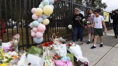 Students and parents place flowers outside Banksia Road Public School in Greenacre where two boys were killed.