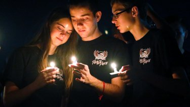Attendees comfort each other at a candlelight vigil for the victims of the shooting at Marjory Stoneman Douglas High School in Parkland, Florida.