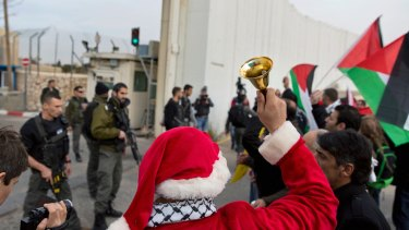 Palestinian protesters, some are dressed as Santa Claus, carry Palestinian flags and chant anti-Israel slogans in front of an Israeli checkpoint, in Bethlehem, West Bank, on Friday.