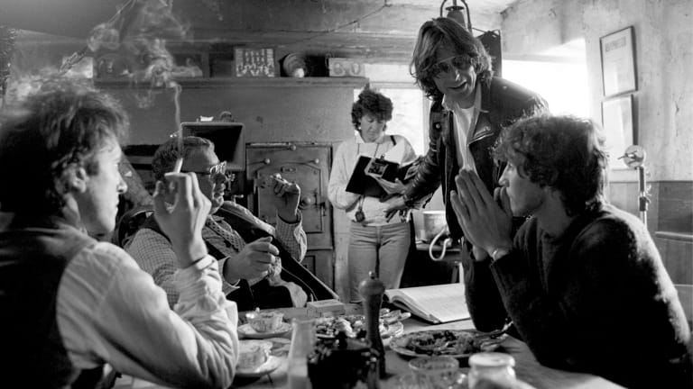 From left, Richard E. Grant, Richard Griffiths, Bruce Robinson (standing) and Paul McGann on the set of <i>Withnail & I</i>.