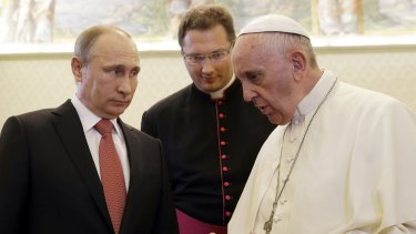Russian President Vladimir Putin (left) listens to Pope Francis at the Vatican.