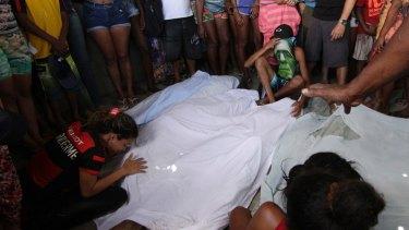 Relatives and friends gather next to bodies found at the Cidade de Deus slum in Rio de Janeiro on Sunday.