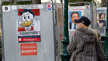"A woman looks at a poster with the Disney character Uncle Scrooge fixed over the official poster of French presidential election candidate for the far-left coalition ""La France insoumise"" Jean-Luc Melenchon."
