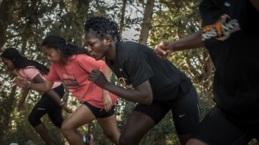 Eighteen-year-old South Sudanese asylum seeker Esteer Gabriel, second from right, prepares to sprint at a sports camp in northern Israel.