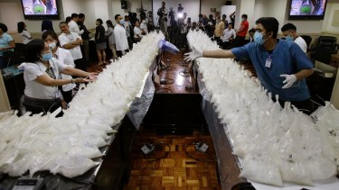 A man passes a box of rubber gloves after they arranged packs of seized methamphetamine at the National Bureau of Investigation in Manila, Philippines on Monday.
