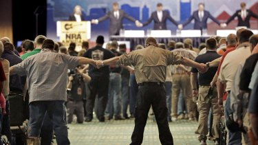 National Rifle Association members hold hands during the opening prayer at the annual meeting of members at the NRA convention on April 11 in Nashville, Tennessee.