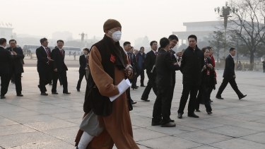 A delegate wearing a mask walks to the Great Hall of the People during severe pollution before the closing session of the National People's Congress on March 16.