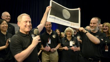 NASA principal investigator for the New Horizons mission Alan Stern (left) and co-investigator Will Grundy (right) hold up a copy of a US postage stamp depicting an outdated image of Pluto.