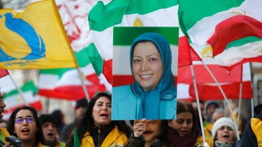 A woman holds up the image of Mujahideen-e-Khalq leader Maryam Rajavi outside 10 Downing Street in London during a demonstration by Britain's Iranian community.