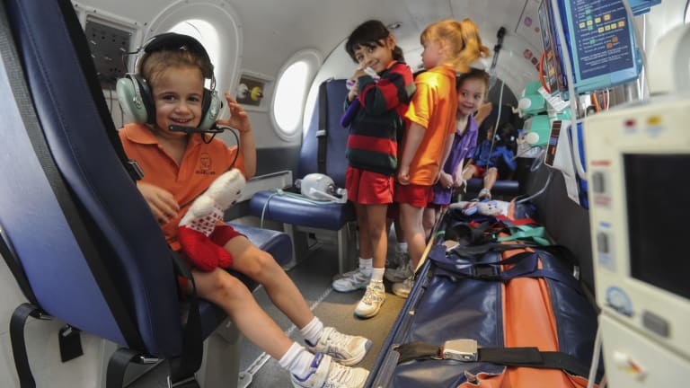 The Royal Flying Doctor Service simulator aircraft touched down at the Canberra Girls Grammar Junior School in Deakin. Prep students got the chance to explore the cockpit and the patient treatment area. Five-year-old Lucia Capezio, left, tries on some headphones.