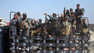 Iraqi National Police officers are transported on the back of a truck on the outskirts of Qayyarah, near Mosul.