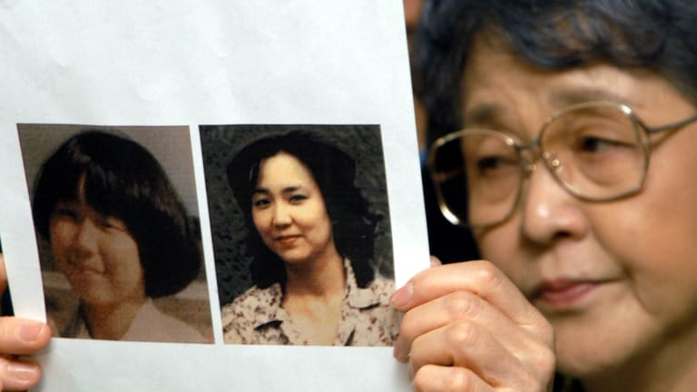In this 2002 photo, Megumi Yokota's mother Sakie shows journalists a picture of her daughter a month before her abduction and a picture purportedly of Megumi as an adult supplied by North Korean authorities. According to Pyongyang, Megumi committed suicide at a mental hospital in 1993.
