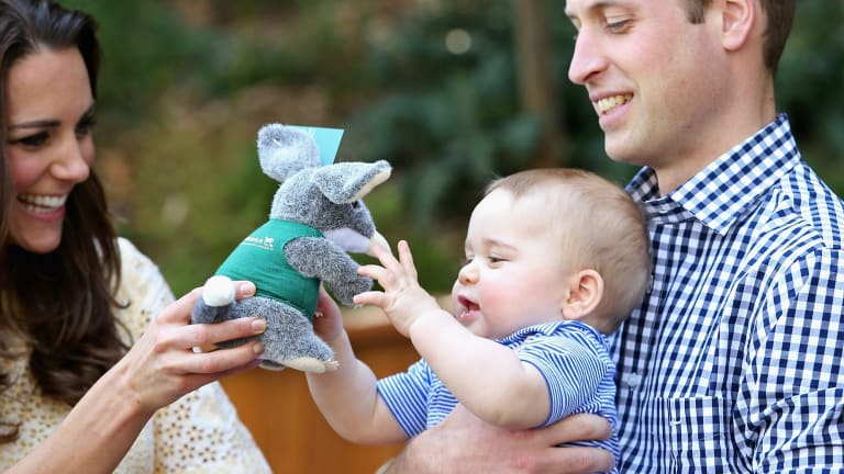 Prince William holds Prince George as his mother Catherine hands him a toy bilby on their visit to Australia last year.